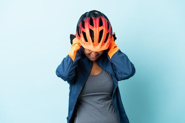 Giovane donna ciclista isolata su sfondo blu frustrata e che copre le orecchie