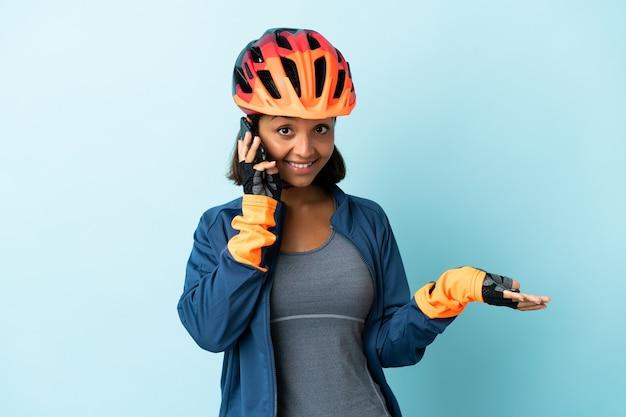Donna giovane ciclista isolata su sfondo blu mantenendo una conversazione con il telefono cellulare con qualcuno