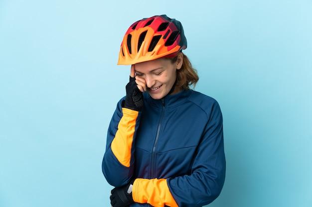 Donna giovane ciclista isolata su sfondo blu ridendo