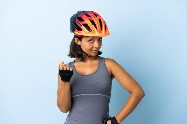 Donna giovane ciclista isolata su sfondo blu che fa gesto di denaro