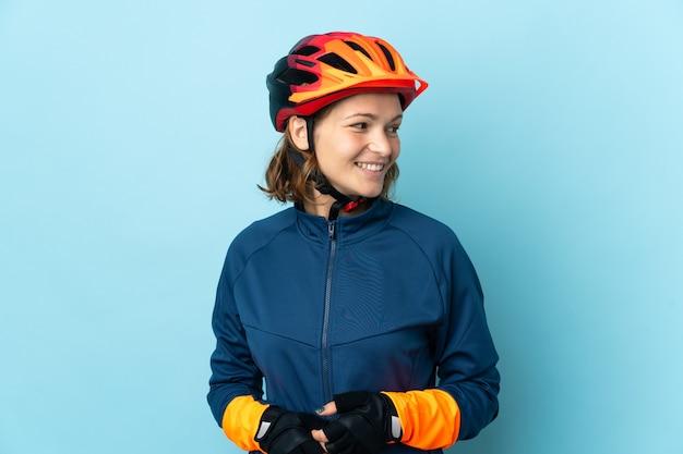 Donna giovane ciclista isolata sulla superficie blu che guarda di lato