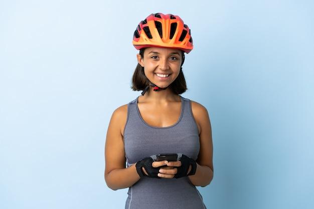 Giovane donna ciclista isolata sulla parete blu che invia un messaggio con il cellulare