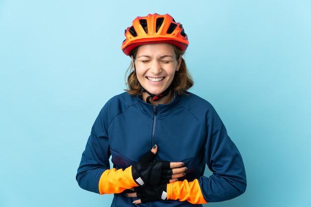 Donna giovane ciclista isolata sulla parete blu che sorride molto