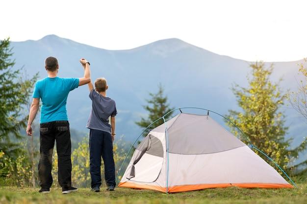 Giovane papà e suo figlio figlio in piedi vicino alla tenda da campeggio con le mani alzate mentre fanno un'escursione insieme in montagna.