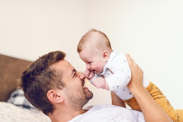 Giovane papà sdraiato nel letto in camera da letto e sollevando il suo amorevole bambino ridere