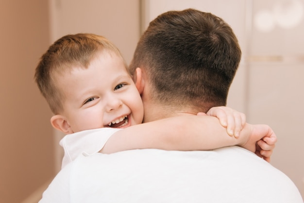 Giovane papà che gioca e che ride con il suo bambino sorridente figlio a casa a letto in camera da letto, famiglia felice