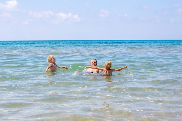 Il giovane papà con i ragazzi biondi nuota nel mare. buone vacanze estive.
