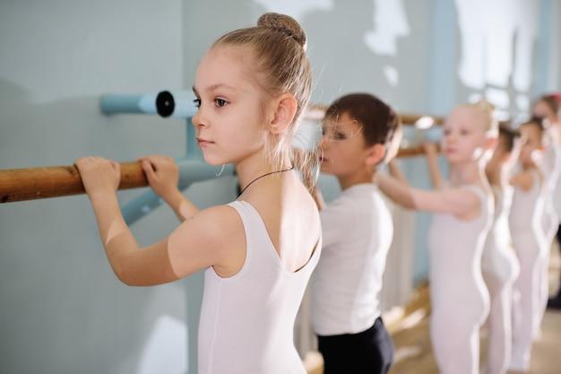 Giovani ballerini nello studio di balletto. i giovani ballerini eseguono esercizi di ginnastica al balletto o alla sbarra durante il riscaldamento in classe.