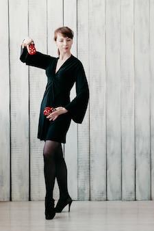 Giovane ragazza che balla in abito nero, con nacchere rosse Foto Premium
