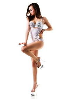 Giovane bella donna castana sottile danzante in costume bianco sexy e scarpe tacchi alti isolate su sfondo bianco