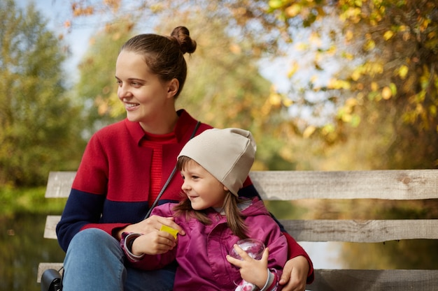 Giovane madre dai capelli scura con la figlia che si siede sulla panca di legno in autunno parco vicino al lago o al fiume