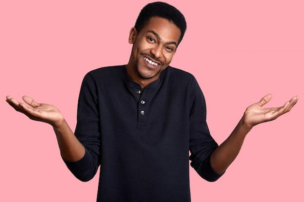 Il giovane maschio dalla pelle scura nella confusione, sta sorridendo isolato sul rosa. bel ragazzo indossa una camicia nera casual e fa un gesto impotente.