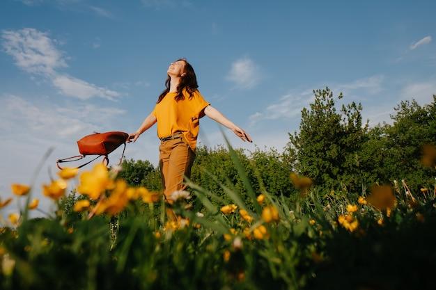 Una giovane donna dai capelli scuri in un vestito giallo con le braccia aperte cammina attraverso il campo guardando l'ora legale dei fiori di campo del cielo soleggiato blu