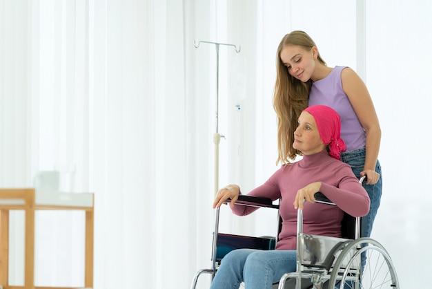 Giovane figlia che abbraccia la sua mamma malata che indossa il velo sulla sedia a rotelle