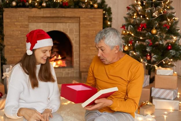La giovane figlia dà a suo padre il regalo di natale, uomo anziano con la scatola regalo di ted
