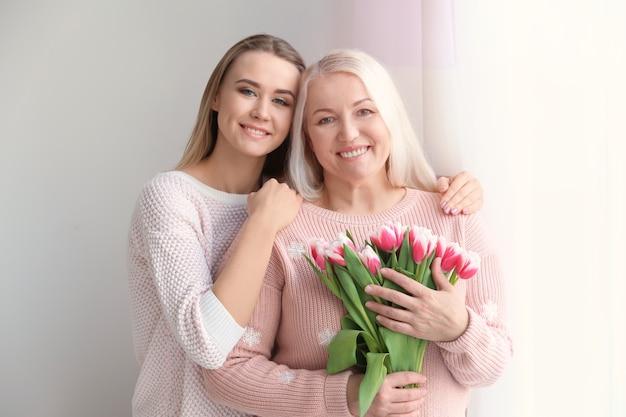 Giovane figlia e madre con un mazzo di fiori a casa