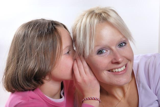 Giovane figlia che bisbiglia nell'orecchio della madre