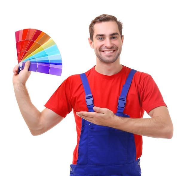 Giovane decoratore che tiene i campioni per la scelta del colore, su bianco