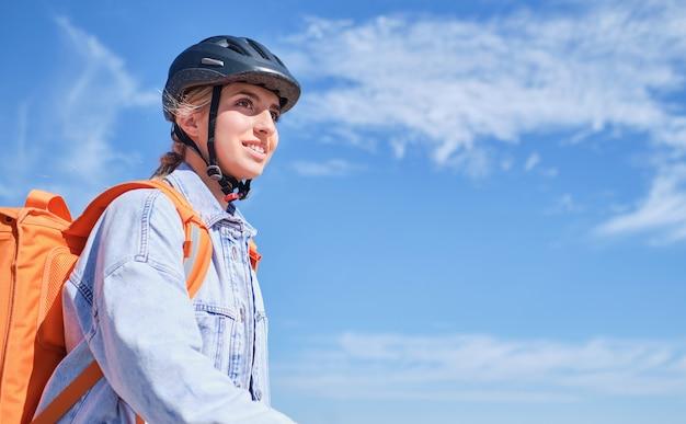 Giovane ragazza delle consegne con zaino isotermico e casco da bici con cielo blu