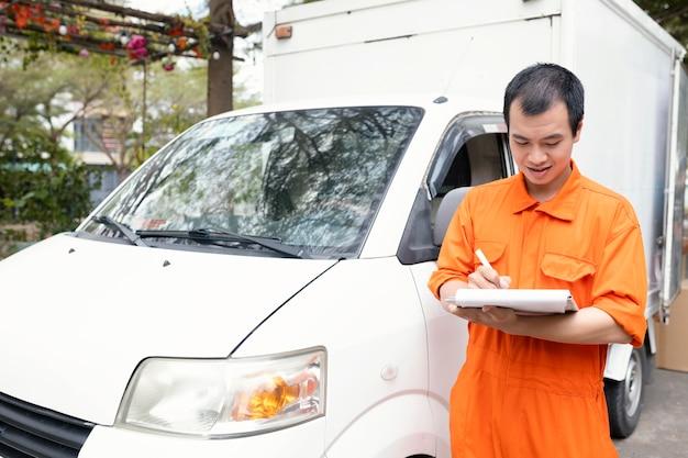 Giovane uomo di consegna che controlla le informazioni sulla consegna