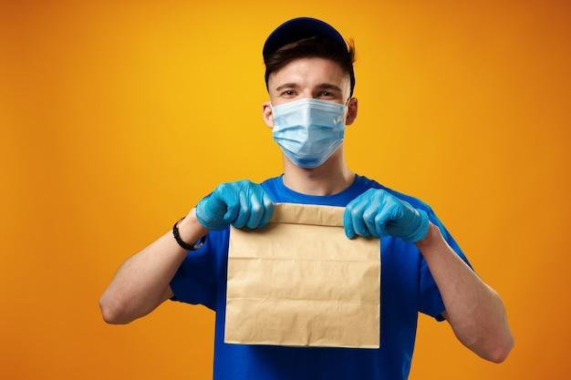Giovane fattorino in maschera facciale e guanti che tengono il pacco di consegna del cibo su sfondo giallo
