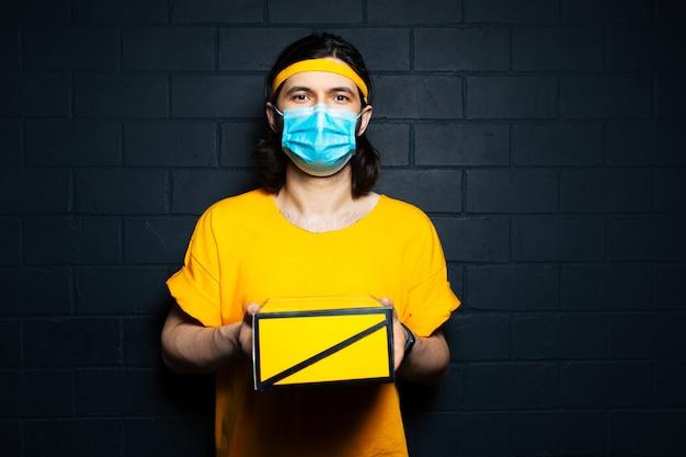 Giovane fattorino che dà una scatola gialla, indossa una maschera medica e una camicia arancione sullo sfondo di un muro di mattoni neri.