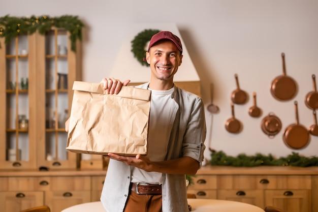 Giovane fattorino che tiene e porta una scatola di cartone. acquista cibo online nel concetto di quarantena.