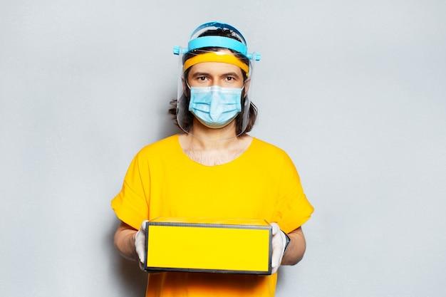Giovane fattorino in possesso di una scatola gialla con maschera facciale su sfondo bianco