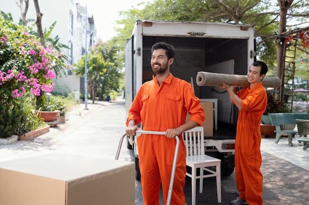 Giovani uomini di consegna che spostano oggetti fuori dalla macchina di consegna