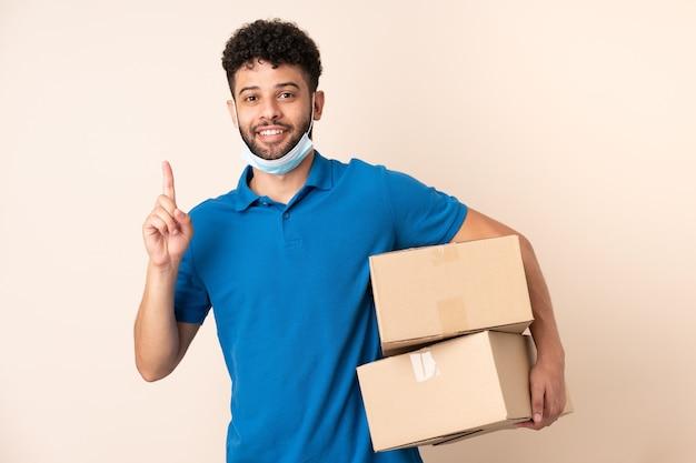 Giovane uomo marocchino consegna isolato su beige che intende realizzare la soluzione alzando un dito