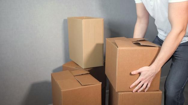 Il giovane addetto al servizio di consegna prende molta scatola di cartone.