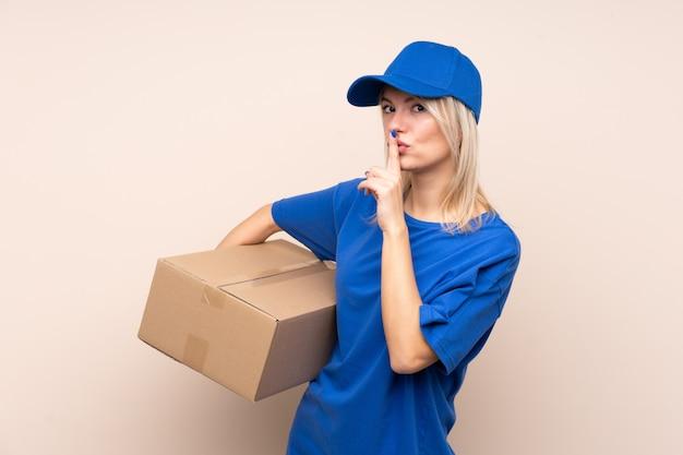 Giovane donna di consegna sopra la parete isolata che fa gesto di silenzio