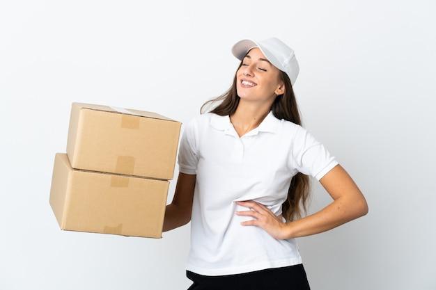 Giovane donna delle consegne su sfondo bianco isolato in posa con le braccia all'anca e sorridente