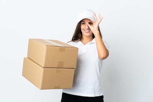 Giovane donna delle consegne su sfondo bianco isolato che mostra segno ok con le dita