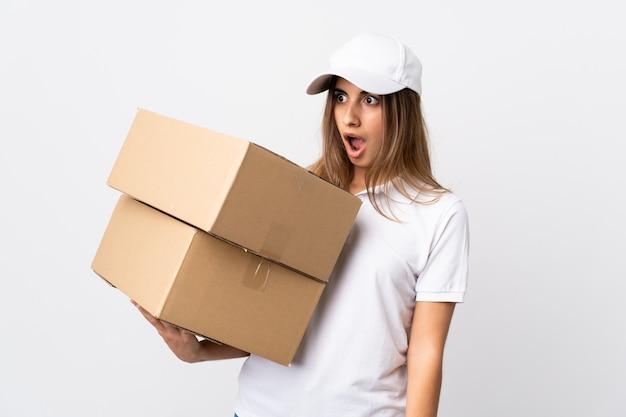 Giovane donna di consegna sopra il muro bianco isolato facendo gesto di sorpresa mentre guardando al lato