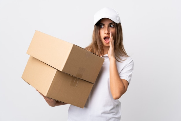 Giovane donna di consegna su bianco isolato sussurrando qualcosa con gesto di sorpresa mentre guardando al lato
