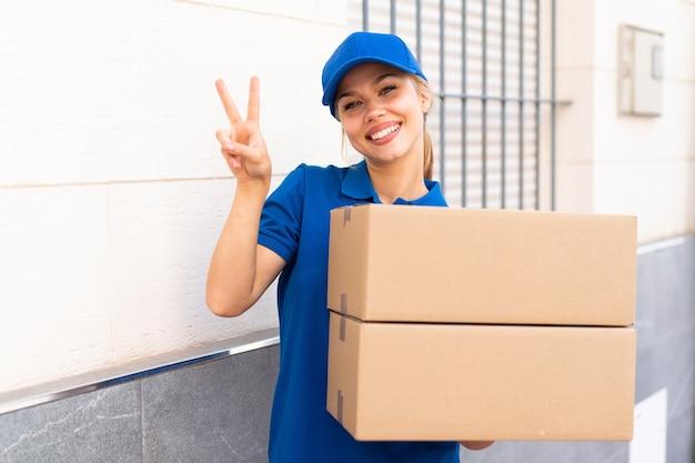 Giovane donna delle consegne all'aperto che tiene scatole e celebra una vittoria