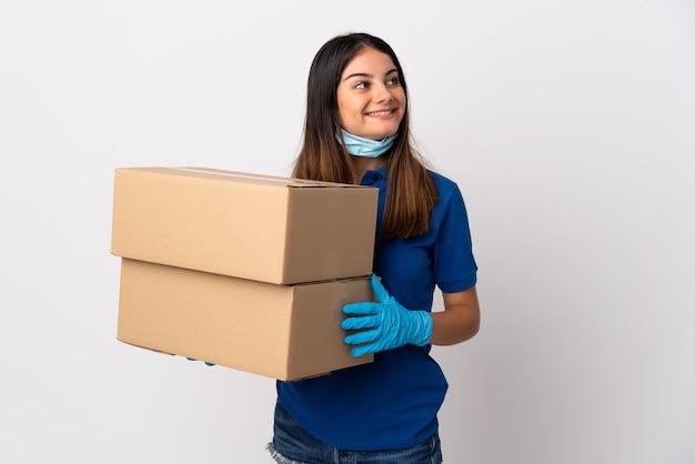 Giovane donna di consegna che protegge dal coronavirus con una maschera isolata su fondo bianco che osserva in su mentre sorride
