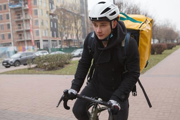 Giovane fattorino che indossa uno zaino termico, in bicicletta per le strade della città in autunno
