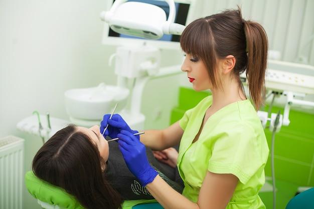 Giovane dentista che cura un paziente femminile nello studio dentistico
