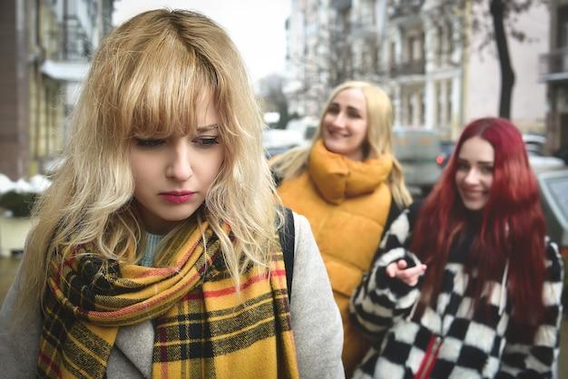 Una giovane studentessa depressa con i capelli biondi vittima di bullismo da parte dei suoi coetanei adolescenti, turbata da sentimenti di disperazione e sofferente di oppressione.