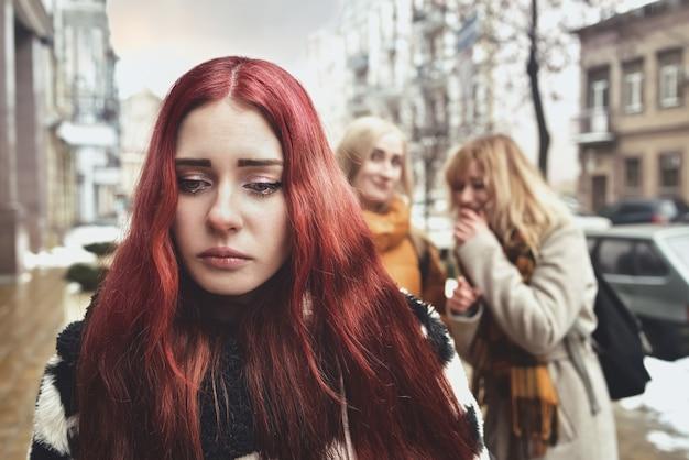 Una giovane studentessa depressa con i capelli rossi vittima di bullismo da parte dei suoi coetanei adolescenti, turbata da sentimenti di disperazione e sofferente di oppressione.