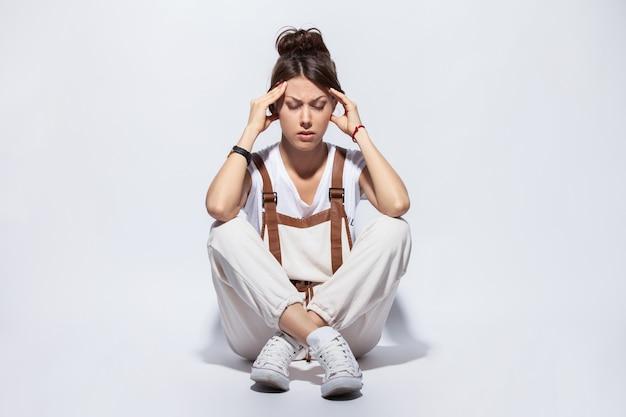 Giovane donna di depressione che si siede sul pavimento.