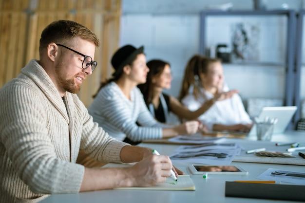 Giovane designer in abbigliamento casual e occhiali da vista disegno schizzo di moda in quaderno su sfondo di donne che lavorano