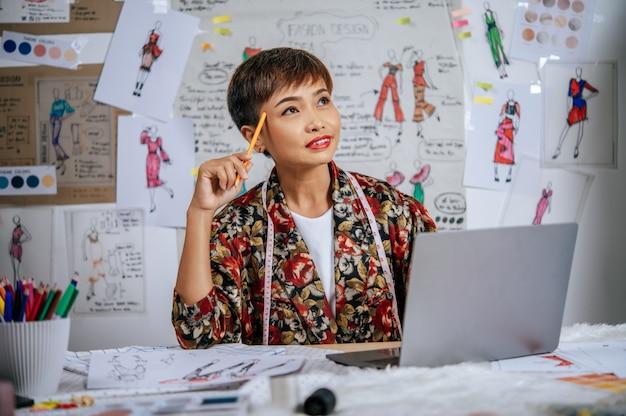 La giovane donna stilista usa il tocco di matita sulla tempia durante il lavoro con il computer portatile per cercare idee per abiti di design sulla scrivania