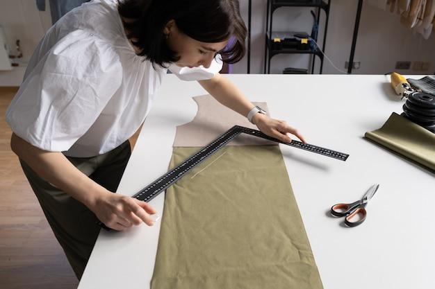 Giovane designer ragazza misura il panno per il taglio sul tavolo in atelier sarta prepara il tessuto da cucire