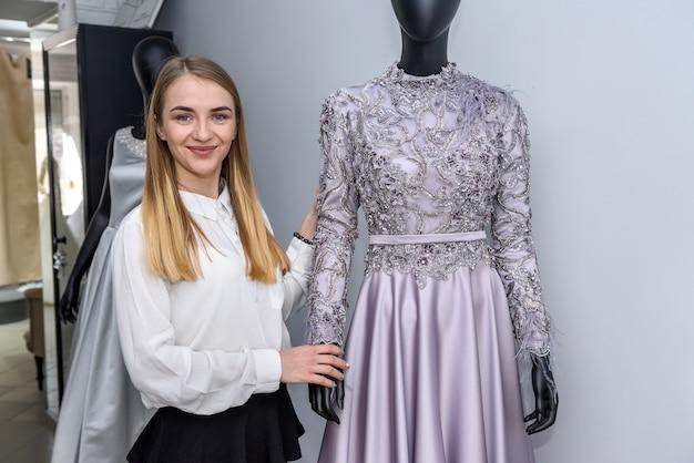 Giovane designer in posa con il manichino nel salone di nozze