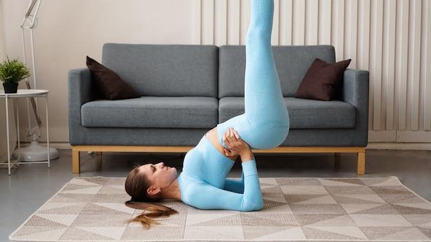 Giovane donna esile sicura determinata che fa gli esercizi a casa. l'istruttore di fitness si allena a casa durante la quarantena. interni moderni e luminosi