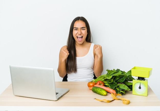 Giovane donna asiatica dietista isolata su sfondo bianco tifo spensierato ed emozionato. concetto di vittoria.