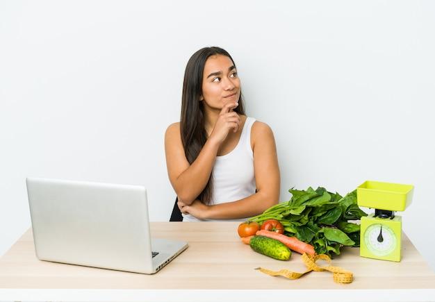 Giovane donna asiatica dietista isolata su priorità bassa bianca che osserva obliquamente con espressione dubbiosa e scettica.